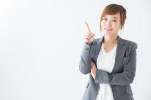 人差し指をたてる女性会社員