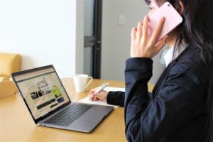 パソコンの前で電話する女性