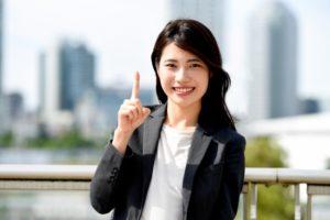 人差し指を立てる女性会社員